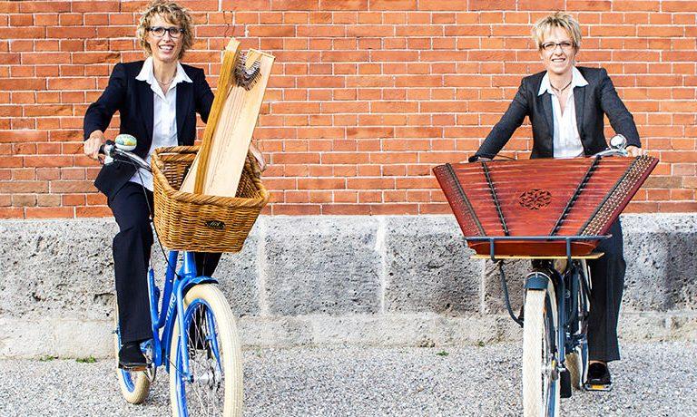 Eva Kastner und Sabine Schmid fahren Harfe und Hackbrett mit dem Fahrrad zum Konzert